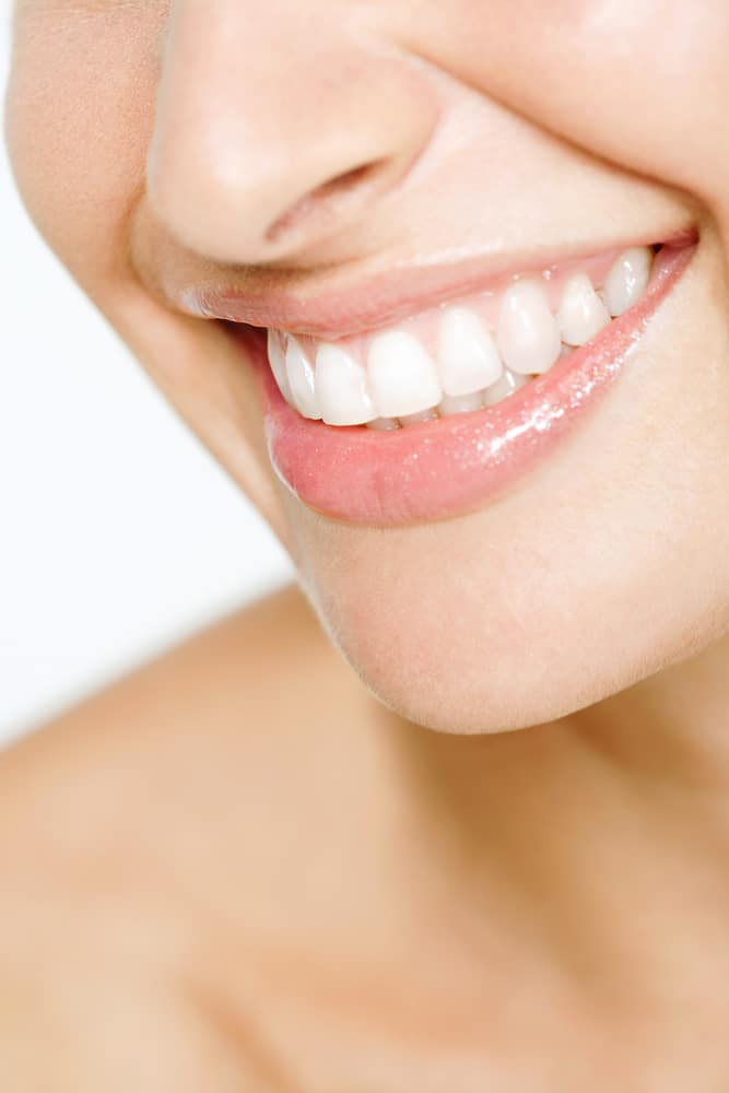 Close up detail view of a young attractive woman half face with a clean white teeth smiling and being expressive wearing soft pink lipstick gloss.