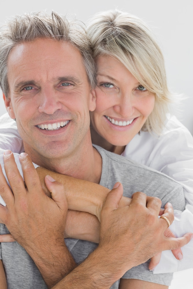 Hugging couple smiling at camera at home in bedroom